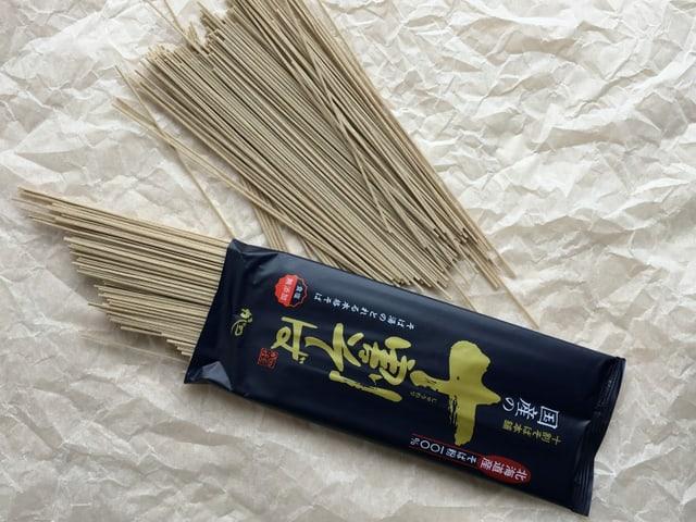 Ein japanisch beschriftetes Pack mit dunklen Soba-Nudeln aus Buchweizen.