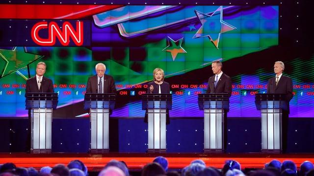 Ils candidats dals democrats sin ina tribuna.