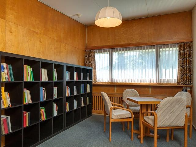 Bibliothek mit Büchern und 4 Stühlen um einen kleinen eckigen Tisch.