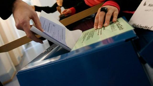 Eine Frau wirft ihren Wahlzettel in eine Urne.
