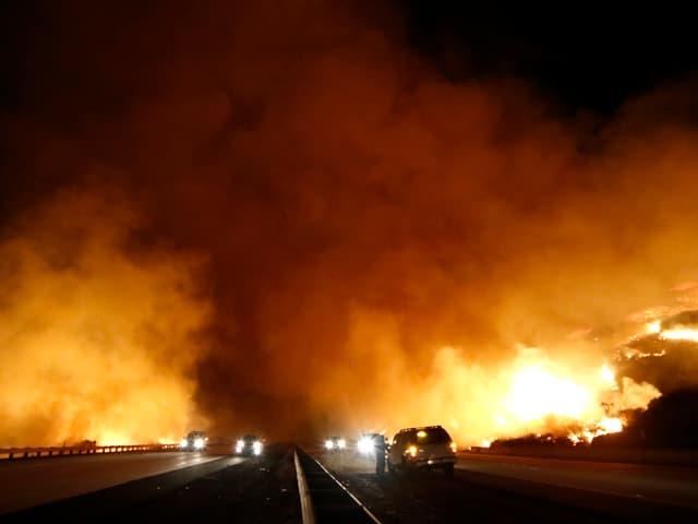 Highway bei Nacht, links und rechts Feuer.