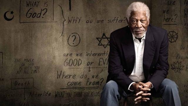 Morgan Freeman sitzt mit verschränkten Händen vor einer Mauer auf der religiöse Symbole und Zeichen sind.