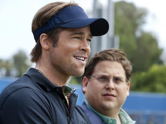 Brad Spitt steht mit einem Baseball-Cap neben Jonah Hill.