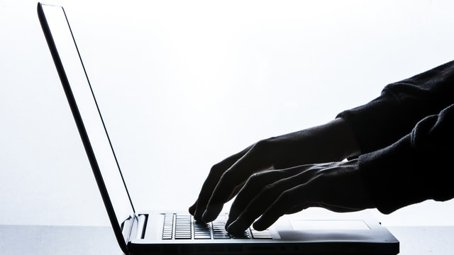 Mauns vid la tastatura dad in laptop.