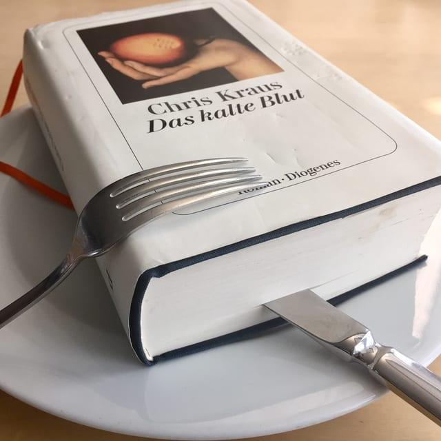 «Das kalte Buch» von Chris Kraus liegt auf einem Teller. Das Messer steckt im Buch.