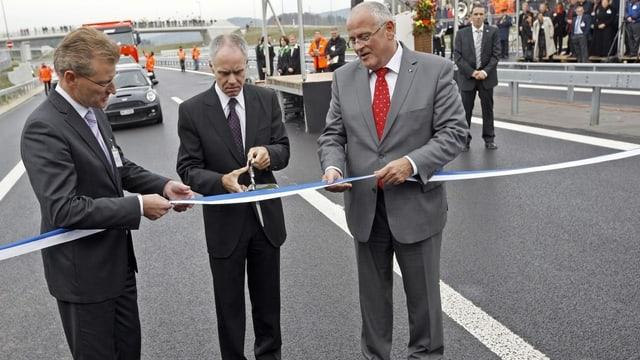 Drei Männer stehen auf der Autobahn und zerschneiden ein Band.