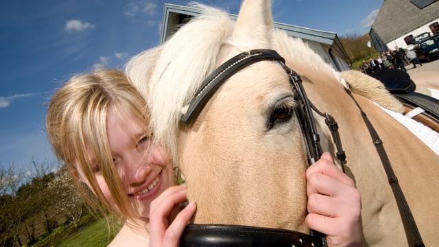 Ein Mädchen streichelt ein Pferd am Kopf und freut sich darüber.