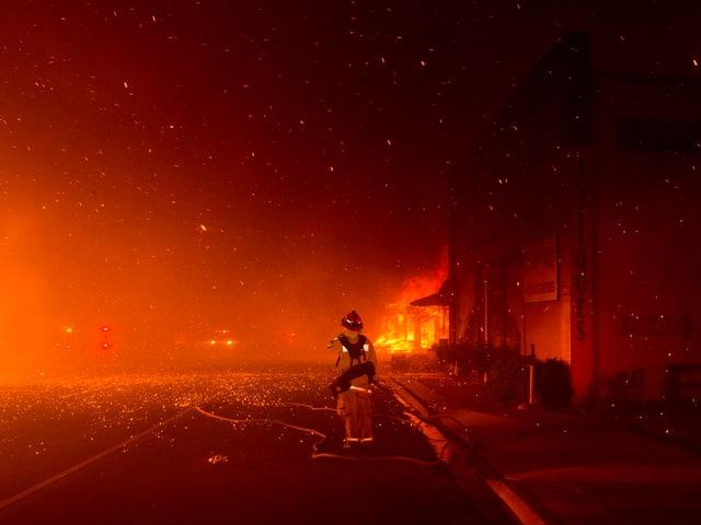 .Feuerwehrmann vor einem brennenden Gabäude.