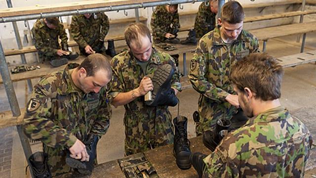 Angehörige der Armee beim Stiefel reinigen.