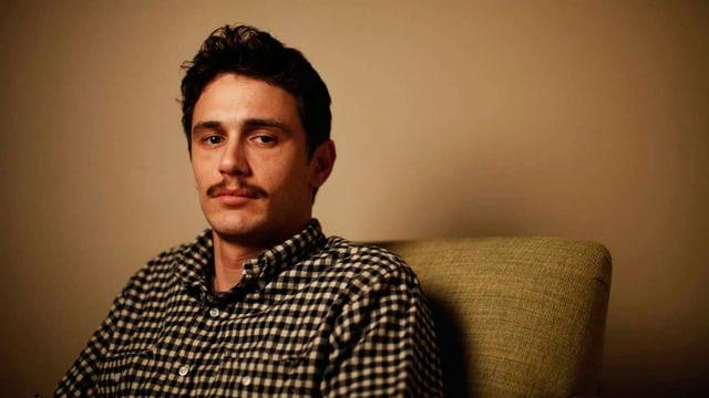 James Franco auf einem grauen Sessel.
