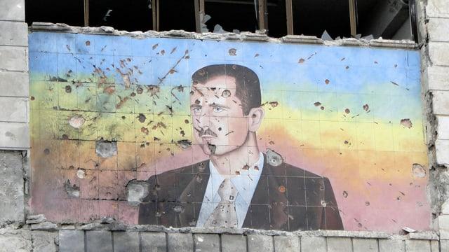 Ein mit Einschusslöchern durchdrungenes Bild von Bashar al-Assad.