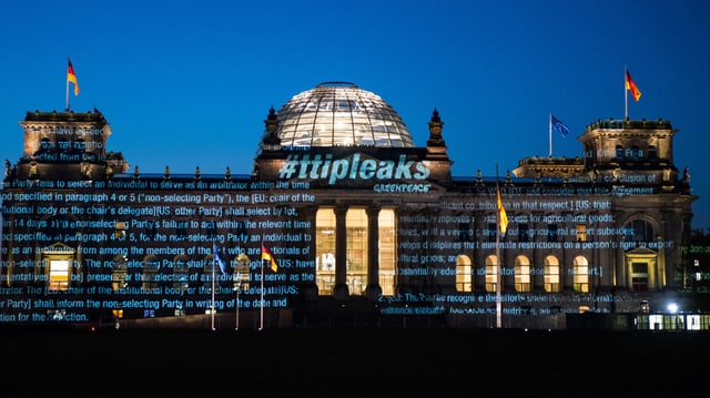 Reichstagsgebäude in Berlin am frühen Morgen – mit darauf projizierten Schriftzügen.
