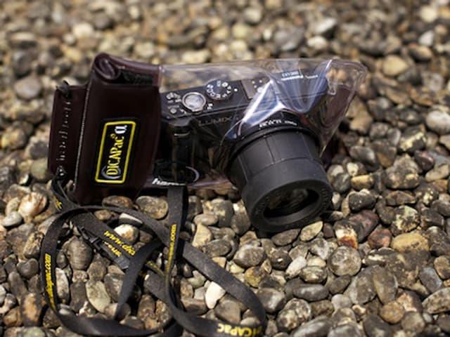 Eine Kompaktkamera in weicher Hülle liegt auf einem Kiesboden.