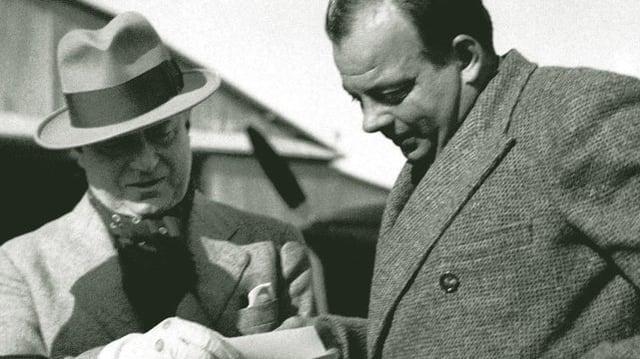 Aufnahme von Saint-Exupéry und Marcel Peyrouton, die gemeinsam in Unterlagen schauen. Im Hintergrund ist unscharf ein Flugzeug zu sehen.