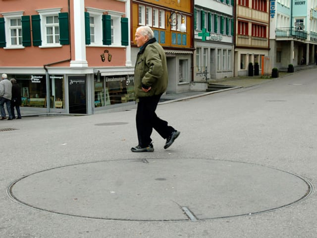 Ein Mann geht an einem runden Kreis im Asphalt vorbei