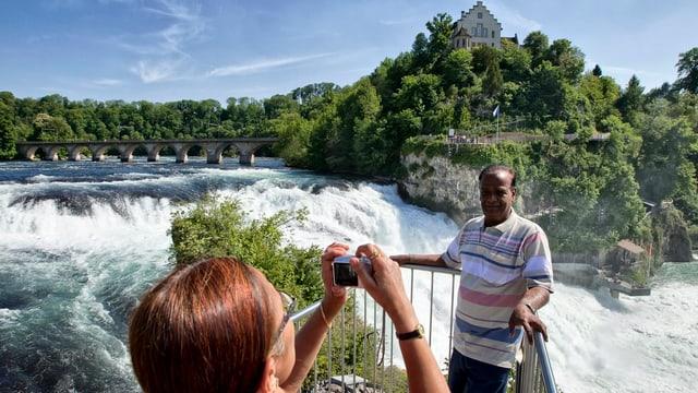 Touristen lassen sich vor einem Wasserfall fotografieren