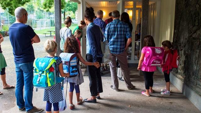 Eltern mit Kindern vor einer Schule am ersten Schultag.