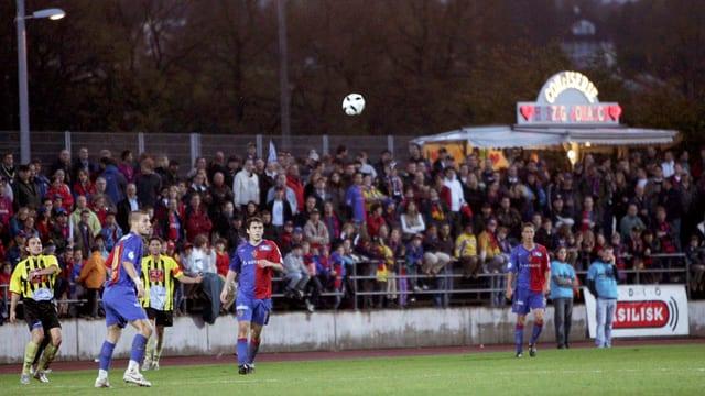 Drei Spieler des FC Basel im rot-blauen und zwei Spieler der BSC Old Boys im gelbgestreiften Trikot sehen in der Schützenmatte Basel einem hochfliegenden Fussball nach, im Hintergrund eine bevölkerte Zuschauertribüne.