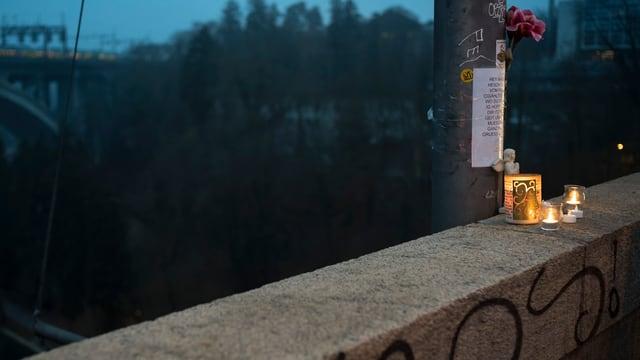 Kerzen und Blumengesteck auf einer Brücke