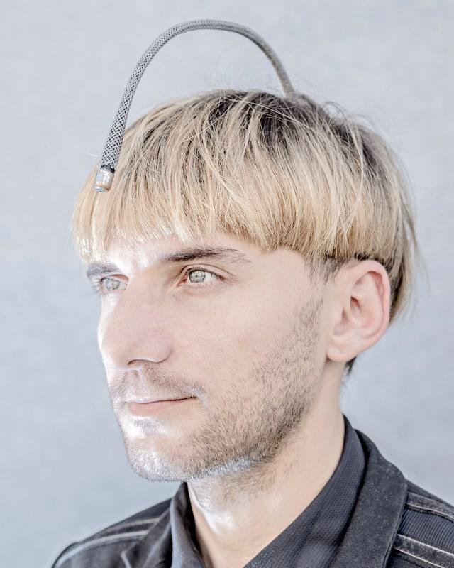 Ein blonder Mann trägt eine gekrümmte Antenne auf dem Kopf.