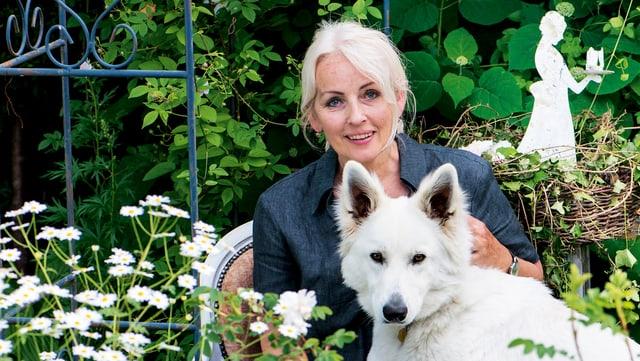 Eine Frau mit einem weissen Hund sitzt in ihrem Garten.