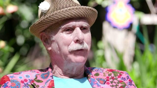 Howard Rheingold trägt ein pinkes Hemd mit Blumen und einen Strohhut.