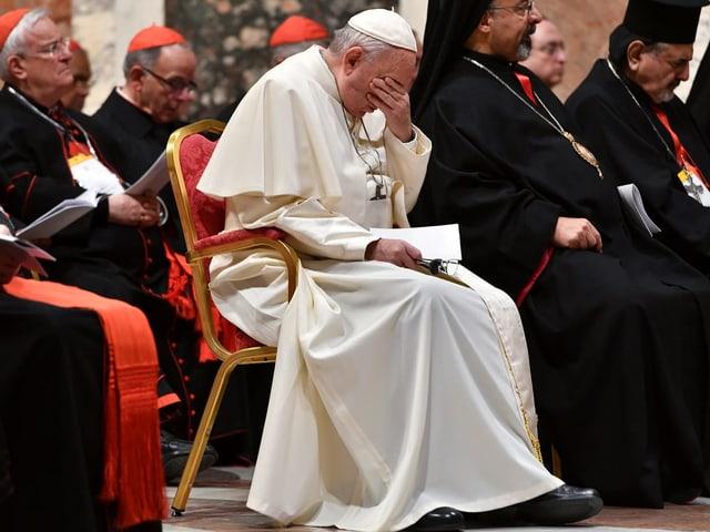 Papst Franziskus stützt das Gesicht in die Hände