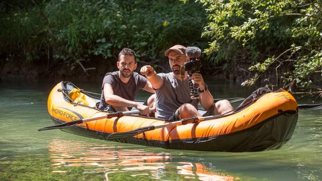 Julien Donzé hinten und Fabien Wohlschlag vorne sitzen in einem orangen Schlauchboot auf einem Fluss. Fabien Wolschlag hält eine Kamera in der Hand.