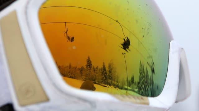Nahaufnahme einer Skibrille, in der sich ein Skilift spiegelt