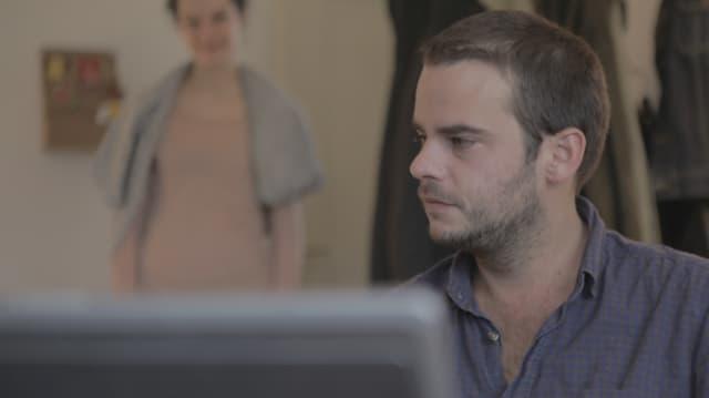 Ein Mann sitzt im Vordergrund vor einem Computerbildschirm, im Hintergrund nähert sich noch verschwommen eine Frau.