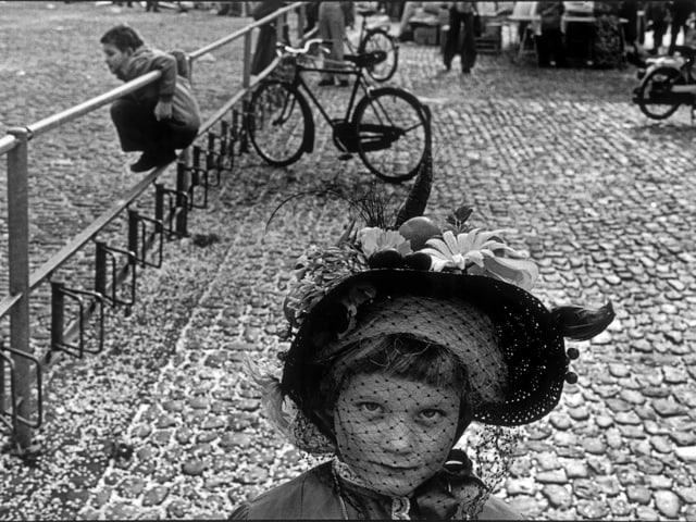 Ein Mädchen mit einem Federhut blickt in die Kamera.