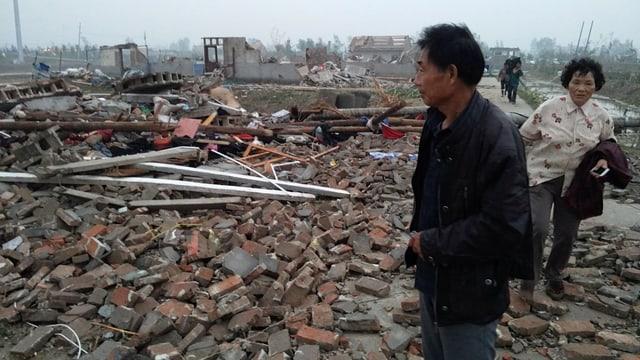 Menschen stehen auf einem Haufen Ziegel, wo vorher ein Haus stand.