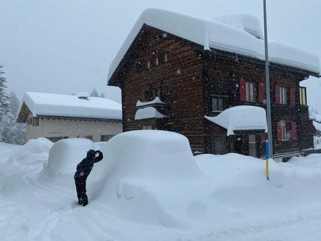 Tief verschneites Dorf mit Auto unter Schneemassen