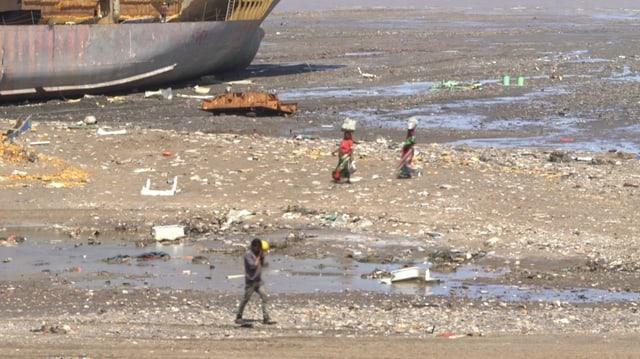 Menschen an einem verseuchten Strand. Zwei Frauen tragen Saris.