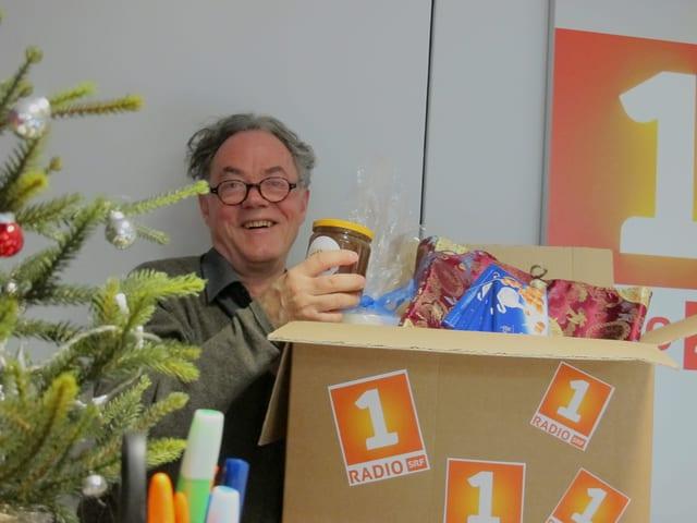 Joseph Reinhardt steht mit dem Paket im Radiostudio und hält ein Glas Honig in der Hand.