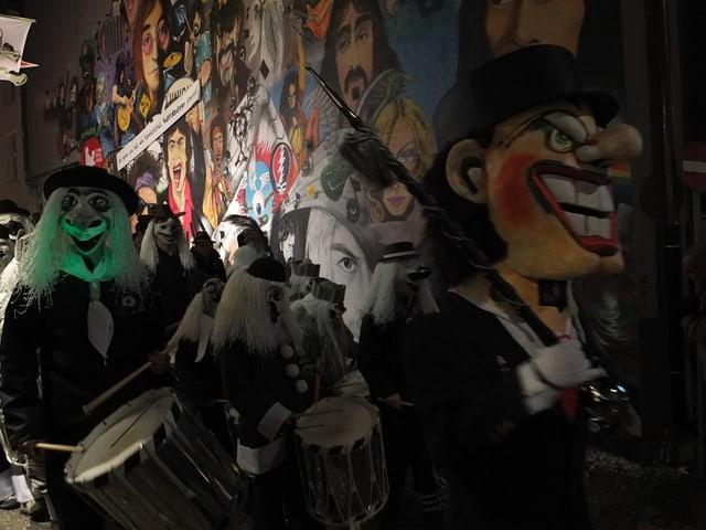 Clique marschiert vor Wandmalerei vorbei mit den Pop-Grössen aller Zeiten.