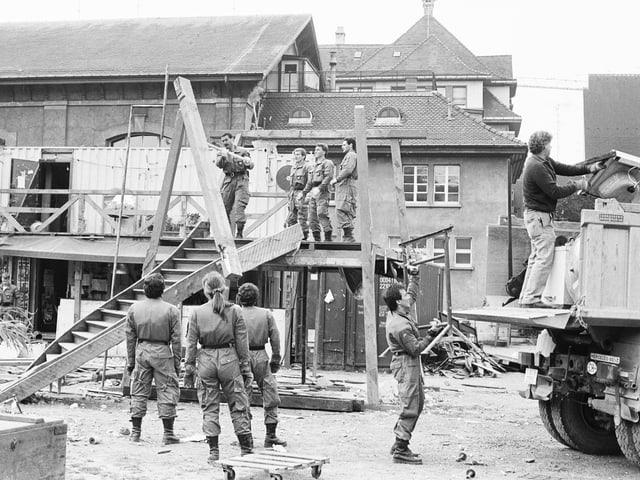 Schwarzweissbild: ein halbes Dutzend Polizisten räumen die Alte Stadtgärtnerei, im Vordergrund ein Holzgestell.