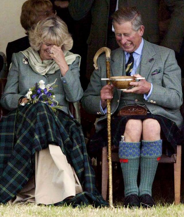 Charles und Camilla sitzen nebeneinander und lachen. Charles hält eine Holzschale in der Hand.