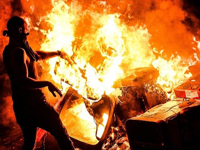 Mann steht vor einer brennende Mülltonne.