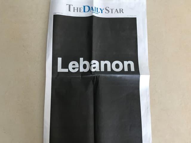 Zeitung mit schwarzer Frontseite.