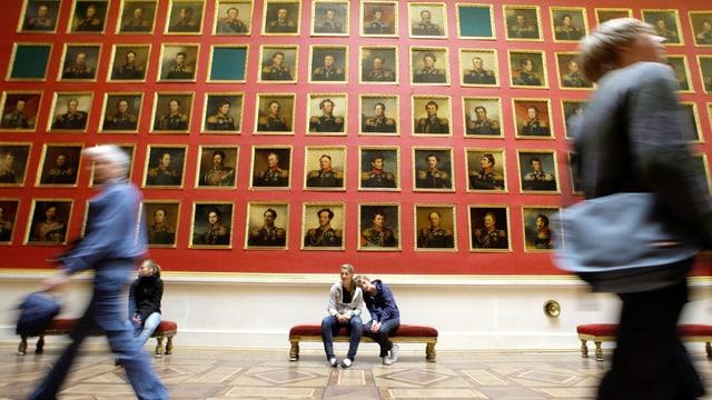 Bilder von Generälen an einer roten Wand in einem russischen Museum.