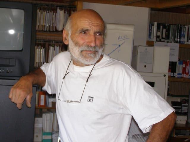 Rolande Desbordes, ein Mann mit weissem Vollbart und weissem T-Shirt, lehnt an einem Schrank.