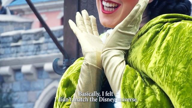 Verkleidete Frau hält Hände zum Geisicht und verzieht ihren Mund zu einem strahlenden Lächeln.