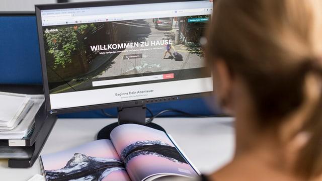 Eine Frau sitzt vor einem Bildschirm.