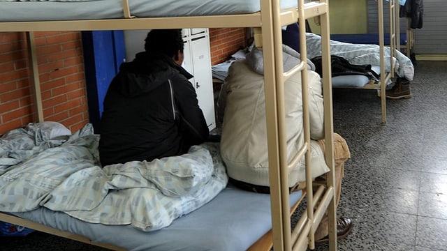 Asylsuchende auf einem Bett.