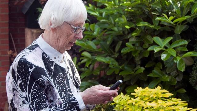 Eine ältere Frau hält ein Telefon in der Hand.