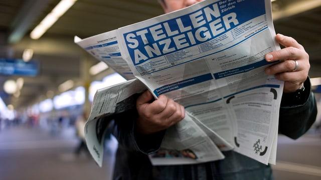Ein Mann liest den Stellenanzeiger an einem Bahnhof.