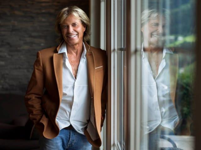 Ein Mann mit blonden Haaren steht an einem Fenster.