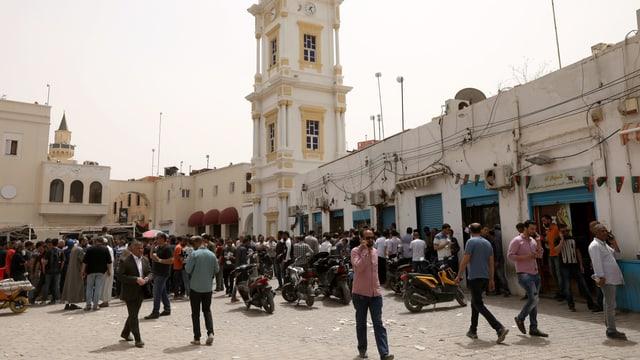 Viele Männer auf einem Platz vor Geschäften.