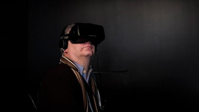 Ein Mann trägt ein Oculus Brille in einem dunklen Raum.